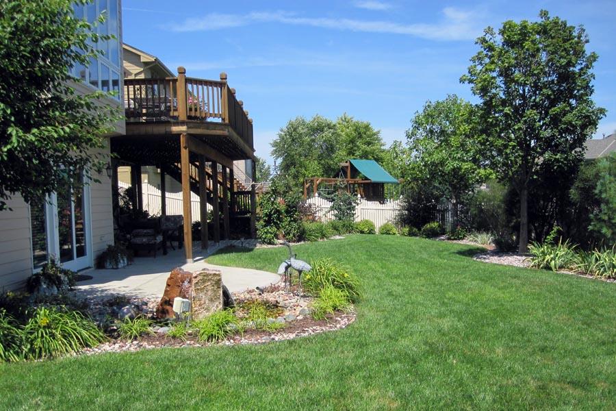 Back yard landscape design with curved rock bed