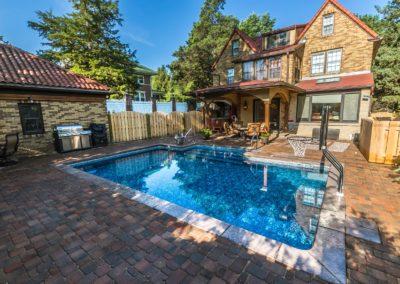 pool with basketball hoop and pavers